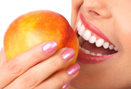 Beautiful young woman eating a peach. Isolated over white