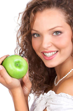 Beautiful young woman eating a green apple. Isolated over white  photo