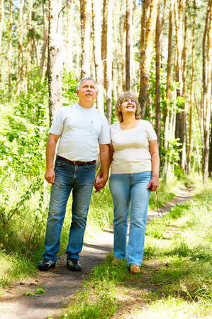 Smiling happy  elderly couple in the forest photo