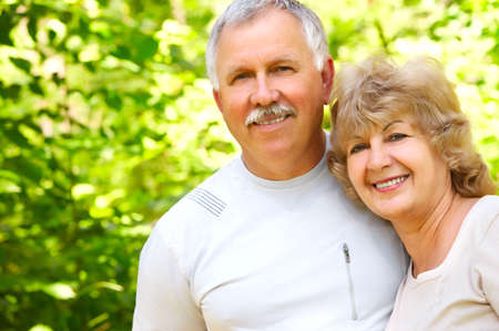 Smiling happy elderly couple in love in the forest  photo