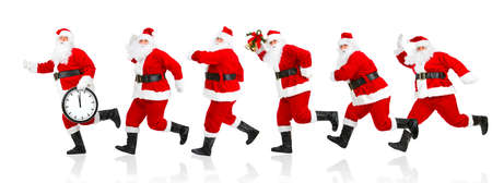 Happy running Christmas Santas. Isolated over white background  Фото со стока
