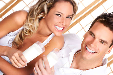 woman drinking milk: Young love couple  drinking milk. Over white background    Stock Photo