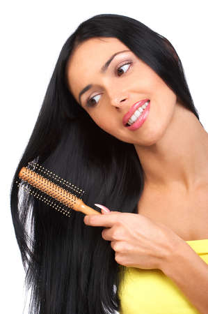comb hair: Young woman combing her hair. Isolated over white backround