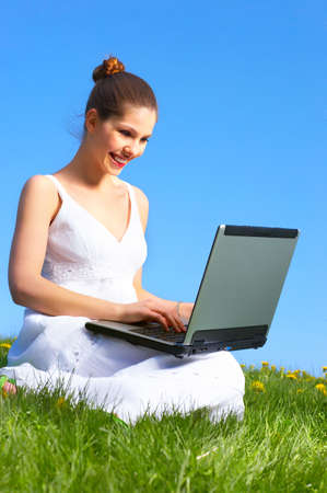 Beautiful young woman working with laptop under blue sky. Stock Photo - 3934248