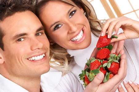 Young love couple eating strawberries. Over white   Stock Photo