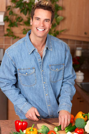 cutting: Young smiling man cooking in the kitchen  Stock Photo