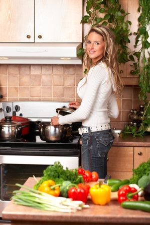 potherbs: Joven mujer sonriente cocina en la cocina