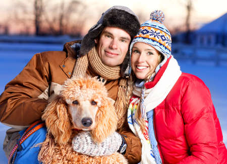 Young  happy smiling couple with dog. Winter  photo