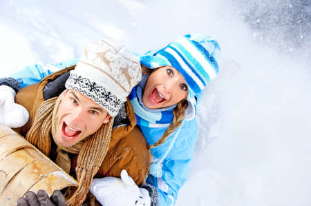 winter: Young  happy smiling couple sledging. Winter