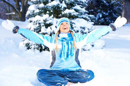 Beautiful laughing happy  woman sitting on snow  photo