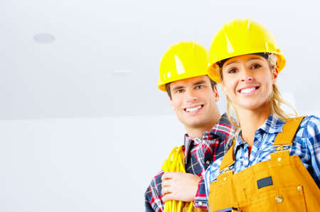 yellow helmet: Young smiling builder people in yellow uniform