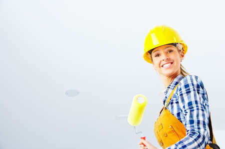 Young builder woman in yellow uniform. Over white background  photo