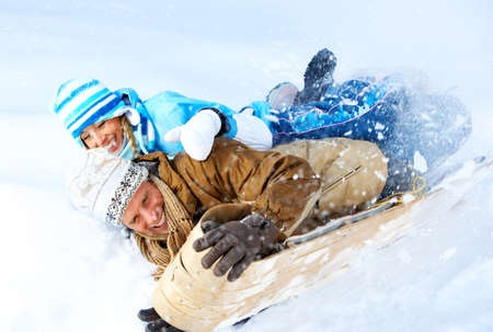 winter fashion: Young  happy smiling couple sledging. Winter