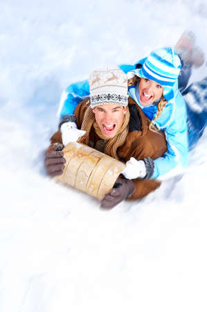 sledging people: Young  happy smiling couple sledging. Winter