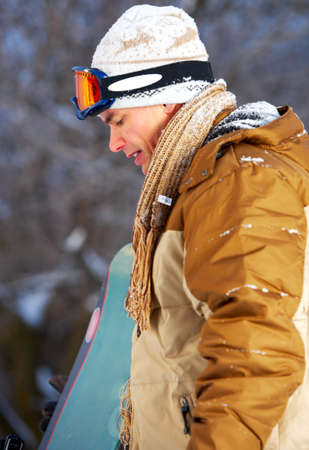 Young  happy smiling man with snowboard. Winter sport  photo