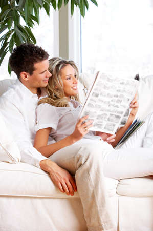 Young love couple reading magazine  in the comfortable apartment  photo