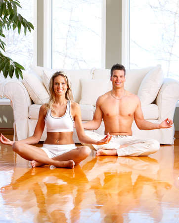Young man and woman woman doing yoga in the sunny room