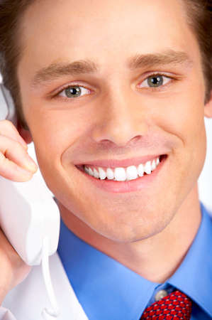 Smiling medical doctor calling by phone. Over white background