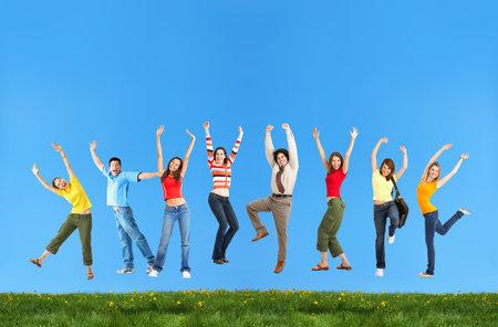 springende mensen: Happy lachende springen jongeren onder de blauwe hemel.