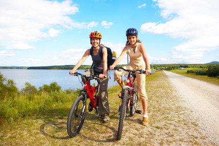 cycleway: Madre e figlia in bicicletta vicino al lago
