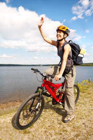Young smiling  woman cycling near the lake   Stock Photo
