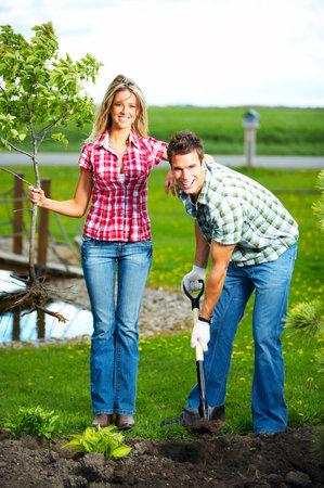 plantando un arbol: J�venes sonrientes personas plantar el �rbol al aire libre Foto de archivo