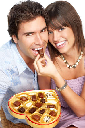 eating chocolate: Happy smiling couple in love. Over white background