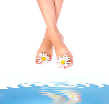 Beautiful woman legs above clean blue water  photo