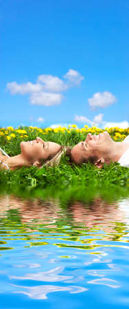 Young love couple sleeping on green grass near water