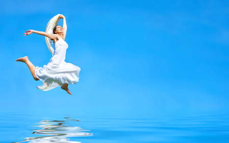 Happy free young woman running across the water  photo