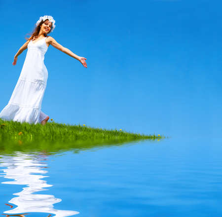 Happy young woman running near the water  photo