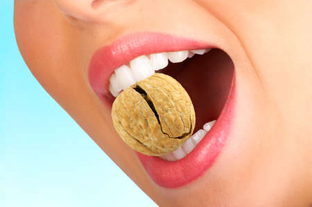 Walnut: Beautiful woman teeth holding a cracked walnut