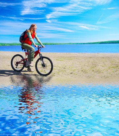cycleway: Giovane donna sorridente in bicicletta vicino al lago