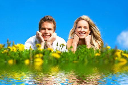 parejas jovenes: Pareja joven sonriente amor bajo el cielo azul Foto de archivo