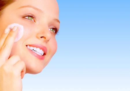 Pretty woman applying cream. Over blue background 免版税图像