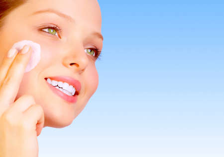 facial: Pretty woman applying cream. Over blue background