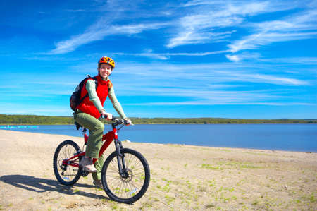 Young smiling  woman cycling near the lake   photo