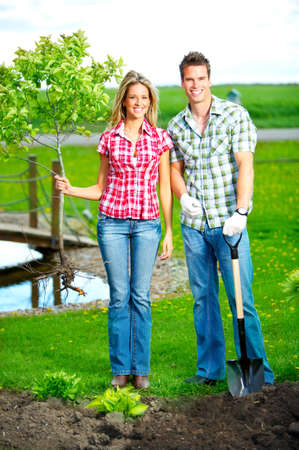 Young smiling people planting the tree outdoor  photo