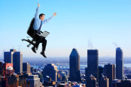 Successful happy  businessman  with laptop flying over the city. 