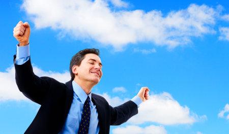 Successful happy businessman under blue sky.   Stock Photo