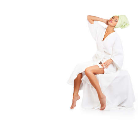 woman in bath: Beautiful young smiling woman in bathrobe. Isolated over white background  Stock Photo