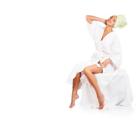 bathrobes: Joven y bella mujer sonriendo en albornoz. Aislado sobre fondo blanco Foto de archivo