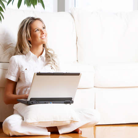 Young beautiful woman working with laptop  in the new  comfortable apartment  photo