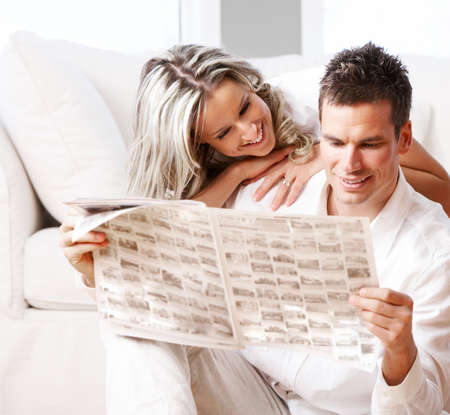 adult magazine: Young love couple reading magazine  in the comfortable apartment