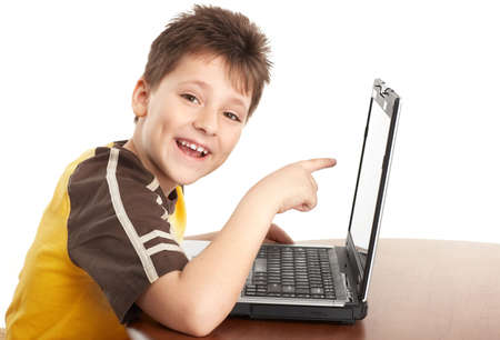 netbooks: Funny smiling boy working with laptop. Isolated over white background