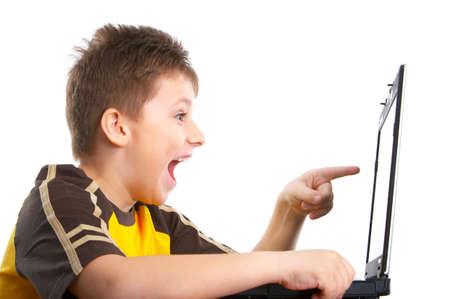 Funny smiling boy working with laptop. Isolated over white background  photo