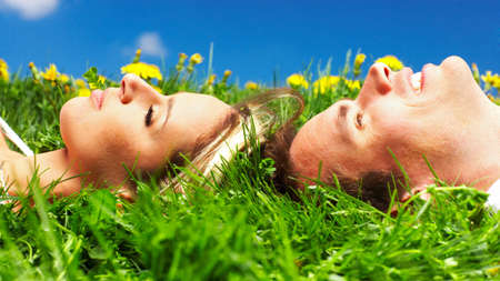 resting: Young love couple smiling under blue sky  Stock Photo