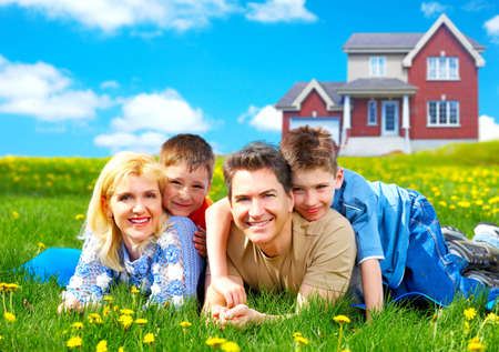 house insurance: Happy family. Father, mother and sons on the green grass