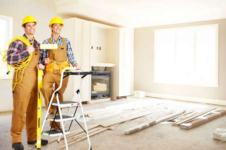 decorates: Young smiling builder people in yellow uniform