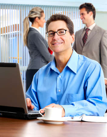 Handsome smiling business man working with laptop.    photo